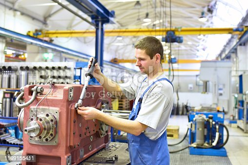 modern mechanical engineering - gear manufacturing factory - assembly by young workers