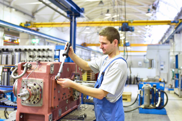 modern mechanical engineering - gear manufacturing factory - assembly by young workers stock photo