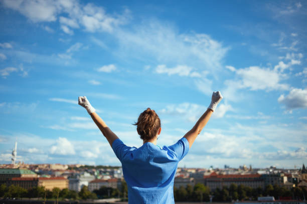 modern medical doctor woman outdoors in city against sky stock photo