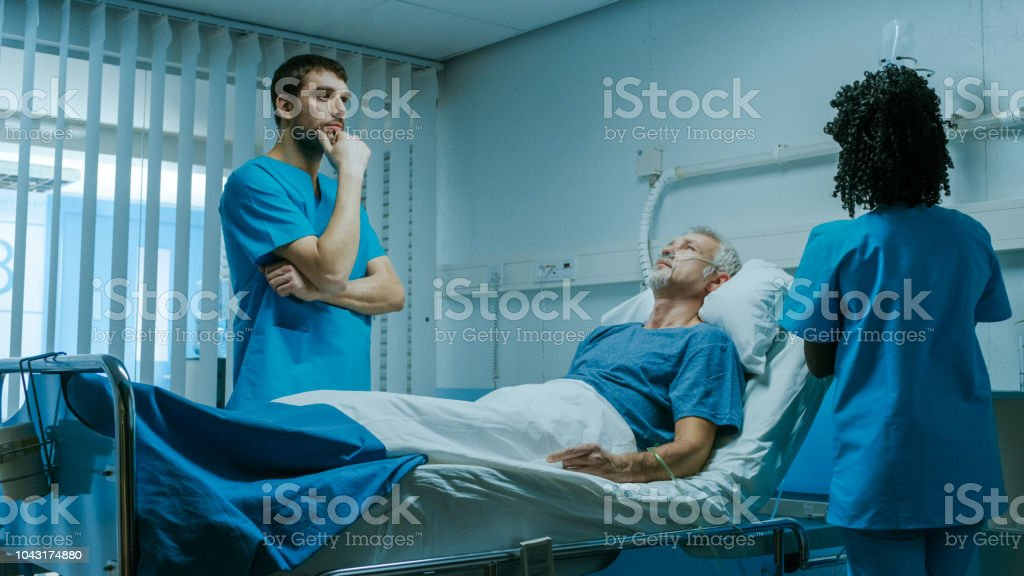 Modern Medical Ward With Sick Patient Lying In Bed And Doctor
