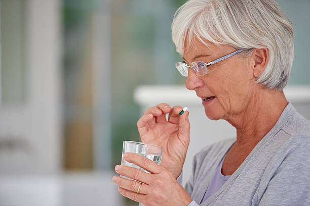 Modern medicine for senior needs Shot of a senior woman about to take a pillhttp://195.154.178.81/DATA/istock_collage/a4/shoots/785189.jpg woman taking pills stock pictures, royalty-free photos & images