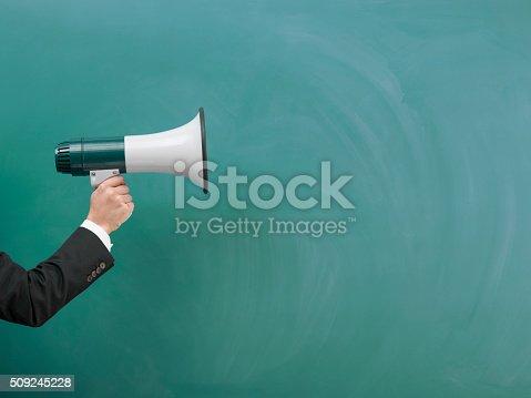 istock Modern Megaphone In Human Hand On Green Blank Blackboard 509245228