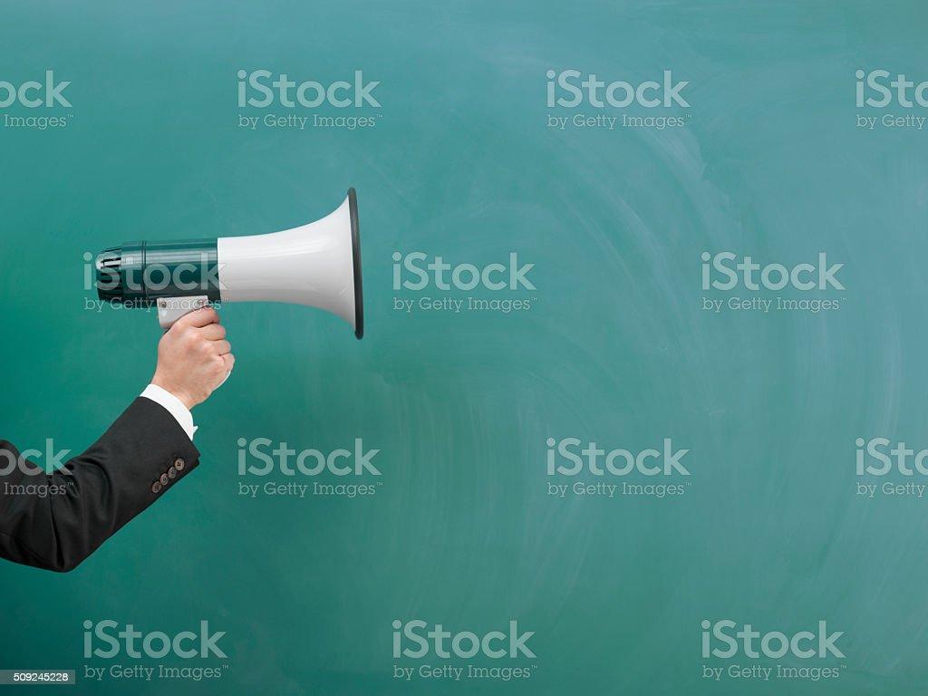 Modern Megaphone In Human Hand On Green Blank Blackboard stock photo