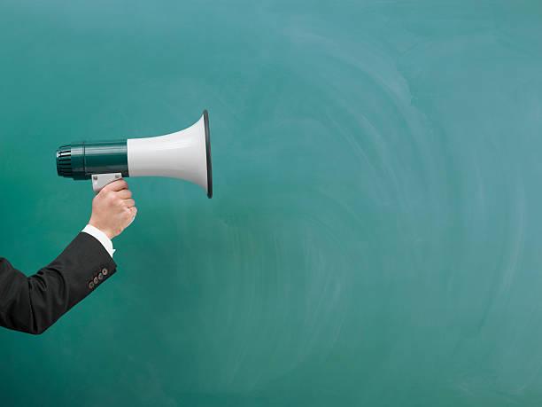 modern megaphone in human hand on green blank blackboard - megafon stok fotoğraflar ve resimler
