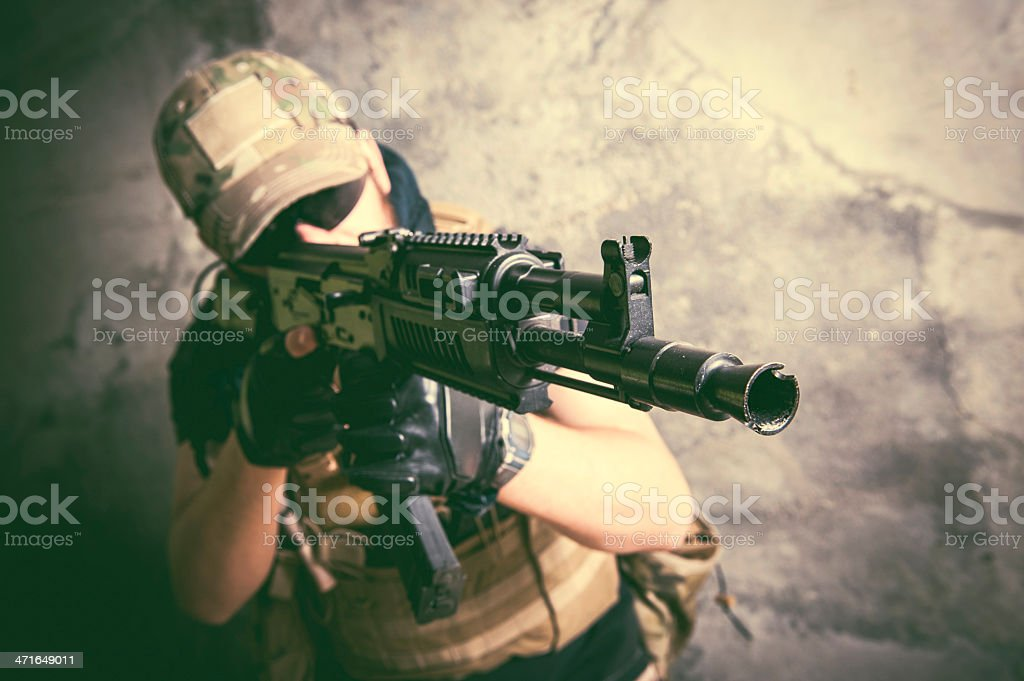 Modern Mercenary Soldier Taking Aim with Assault Rifle stock photo