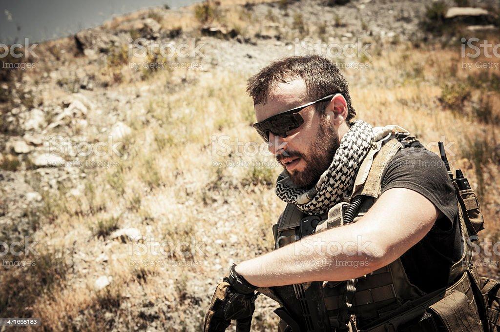 Modern Mercenary Soldier Wipes Sweat From the Effort stock photo