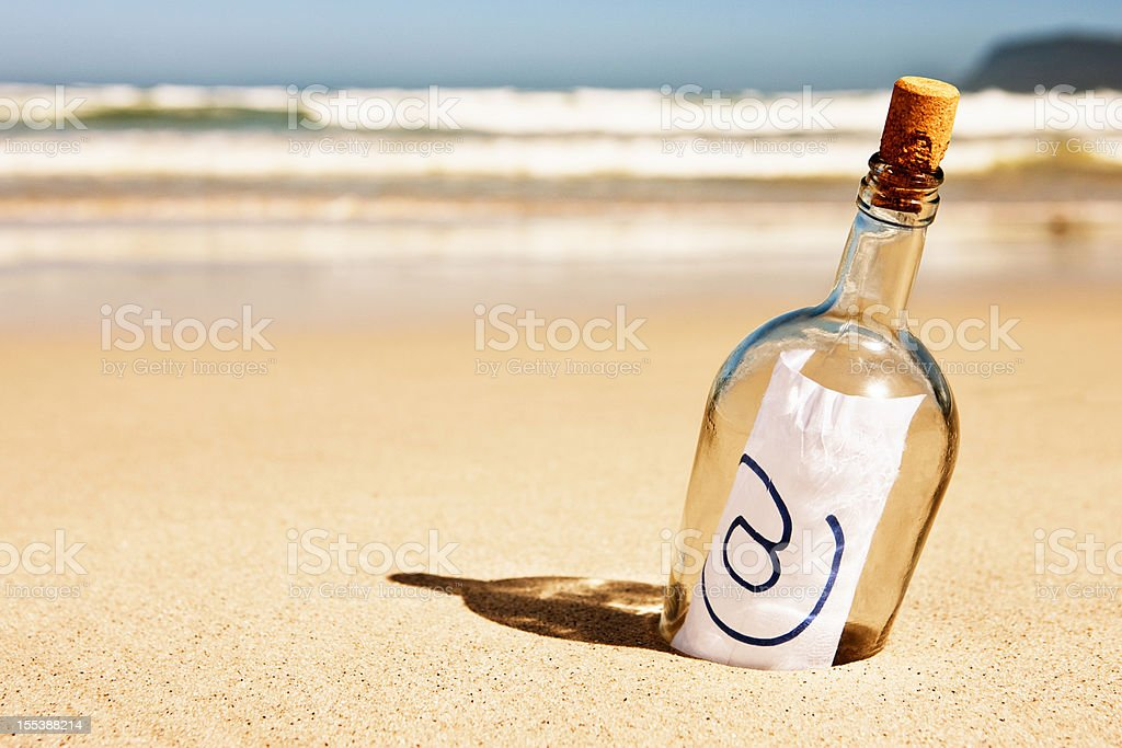 "Modern message in a bottle on beach says simply ""@"" royalty-free stock photo"