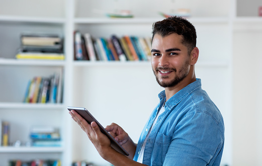 istock Modern mexican hipster man working with tablet computer 1159549042