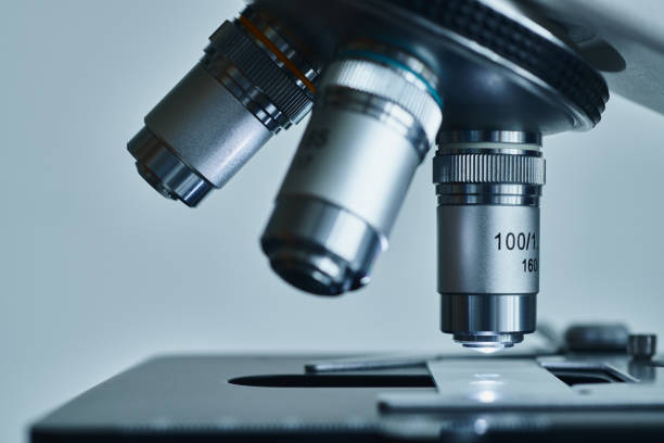 Modern microscope with metal lens at laboratory. stock photo