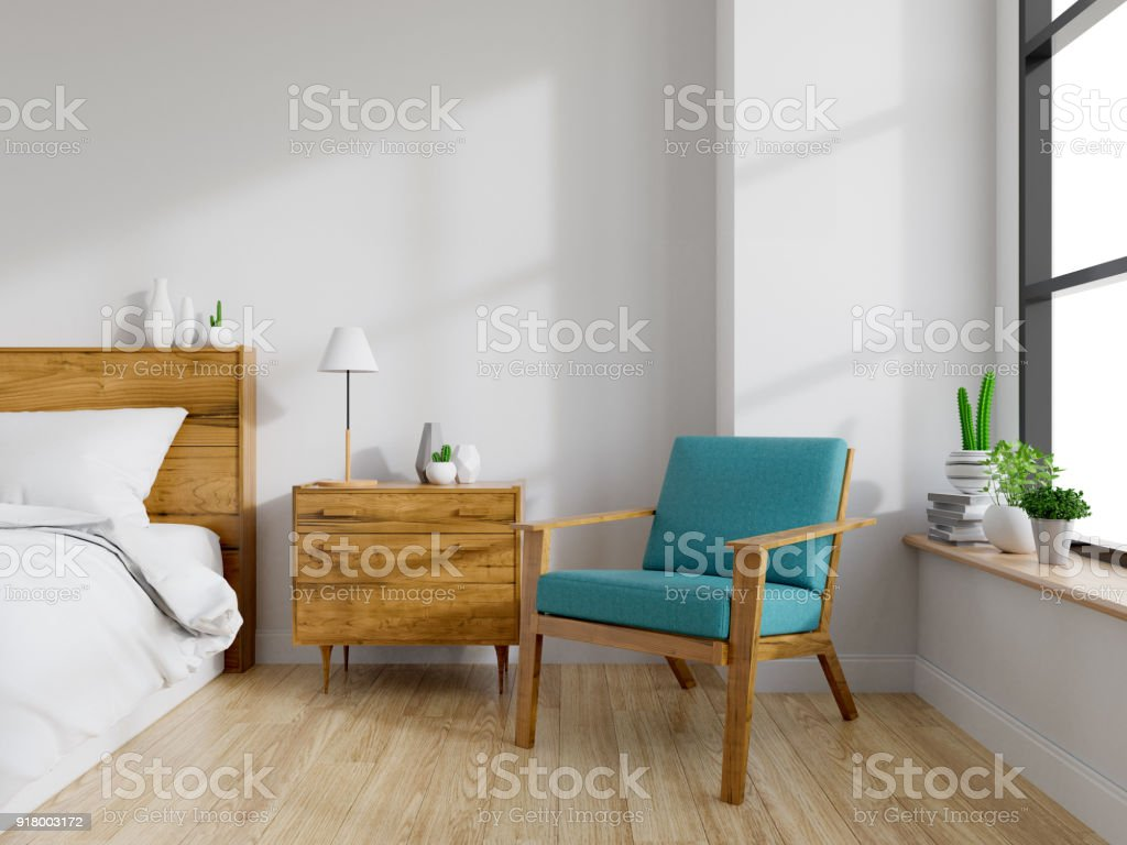 Modern mid Century and vintage interior of bedroom ,blue lounge chair with wood  bedside table and white bed  on white wall and wood floor  in front of a window ,empty room ,3d rendering stock photo