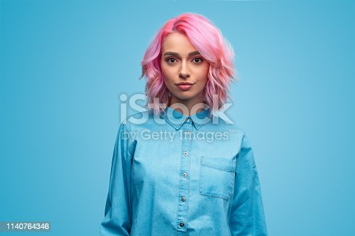 Beautiful young woman with trendy wavy pink hairstyle wearing blue shirt and looking at camera on blue background