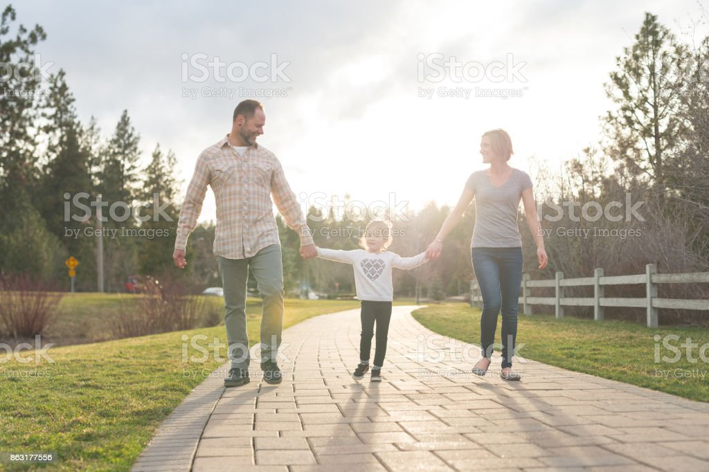 Modern mom and dad walking hand in hand with their young daughter on boardwalk stock photo