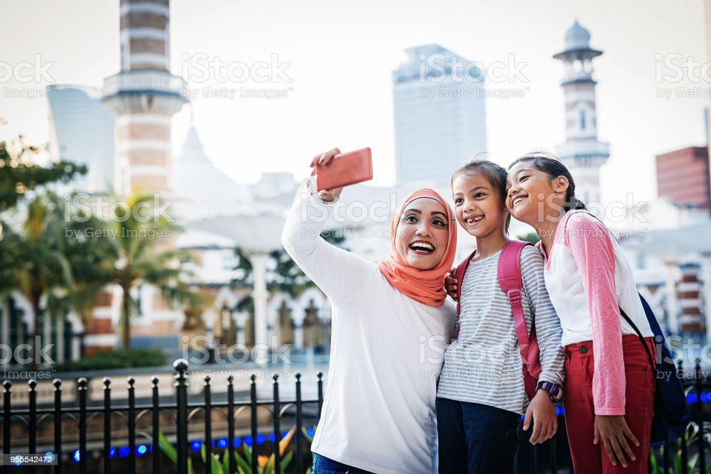 Modern mom in Southeast Asia with daugthers stock photo