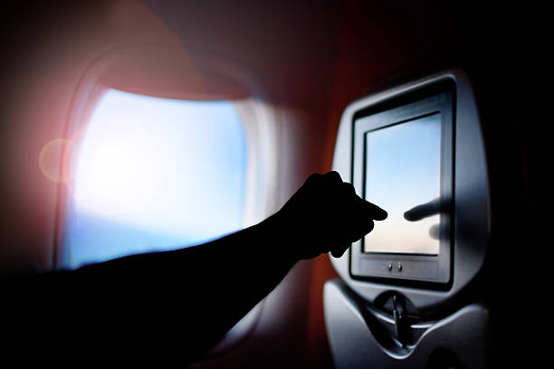 Modern monitor passenger seat on the plane. Airplane window. stock photo
