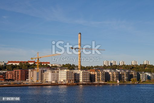 Modern multistorey buildings along sea coast with construction cranes in the final stages of construction