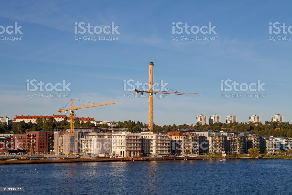 Modern multistorey buildings along sea coast with construction cranes in the final stages of construction stock photo