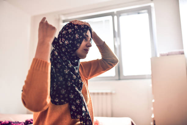 moderna muslimska kvinnliga sätta på en hijab - working from home bildbanksfoton och bilder