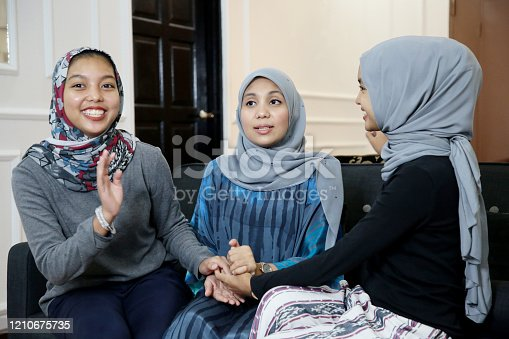 Muslim young women are enjoying spending leisure time chatting at home.