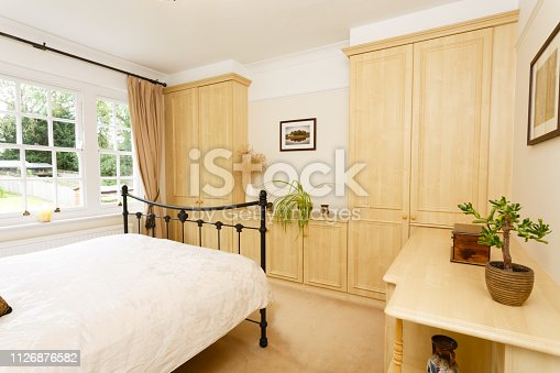 Modern bedroom with neutral colour scheme, cast iron bed and fitted wardrobes
