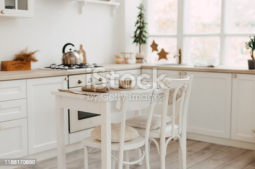 665910118istockphoto Modern new bright kitchen interior with white furniture and a dining table. 1188170650