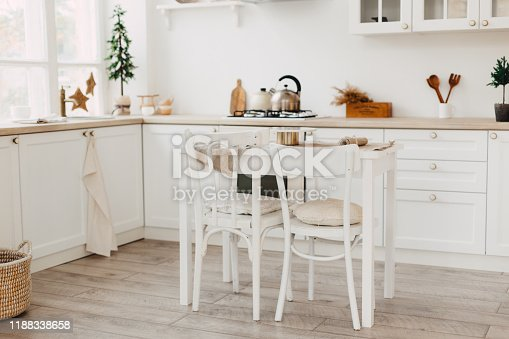 665910118istockphoto Modern new bright kitchen interior with white furniture and a dining table. 1188338658