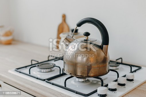 665910118istockphoto Modern new bright kitchen interior with white furniture and a dining table. 1188338671