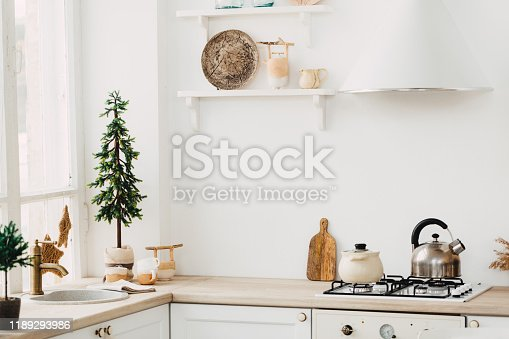 665910118istockphoto Modern new bright kitchen interior with white furniture and a dining table. 1189293986