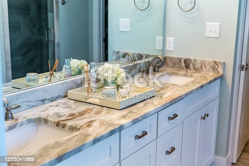 istock Modern new construction home house bathroom with granite countertops and a tile floor and double sinks 1223041989