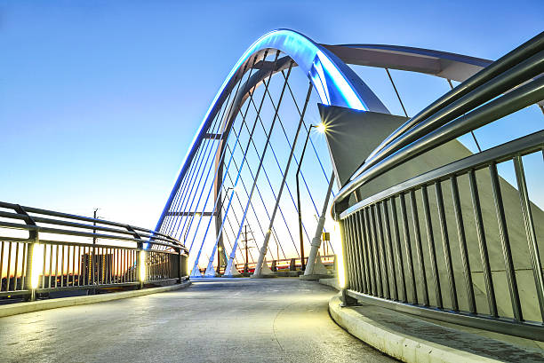 Modern New Lowry Bridge Walkway, Minneapolis. A one of the walkways on the Lowry Avenue Bridge in  Northeast Minneapolis, Minnesota. This bridge connects northeast  to north Minneapolis. The bridge goes over the mighty Mississippi river in a rapidly changing neighborhood thriving with new buildings and commerce. This is a long exposure night shot as the sun just set. elevated walkway stock pictures, royalty-free photos & images