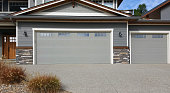 Vernon ,British Columbia, Canada-  September 19,2019: Front exterior view close- up of 3 car garage. One two car garage and one single car garage. Joined to house at front.  Paved driveway in foreground.  Loose packed stone as a feature detail 1/4 way up from bottom. Siding and shingles with windows on the doors.  Partial house and front door left frame. Gray color with white trim.