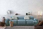Modern Nordic Scandinavian styled apartment, large sofa with blank wall behind. Interior with many details, coffee table, plant, books, pastel colors. Copy space mock up for designers