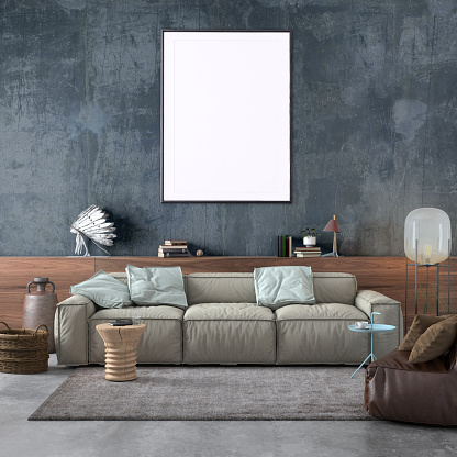Modern Nordic style apartment interior. Large pastel colored sofa with chair. Concrete textured wall with picture frame template for copy space. Wooden shelf with books, electric lamp and lots of other details. Designer artist background template.