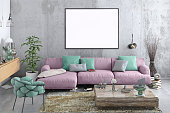 Modern Nordic style apartment interior. Large pastel colored sofa with armchair. Concrete textured wall with picture frame template for copy space. Books, plant and lots of other details. Designer artist background template.