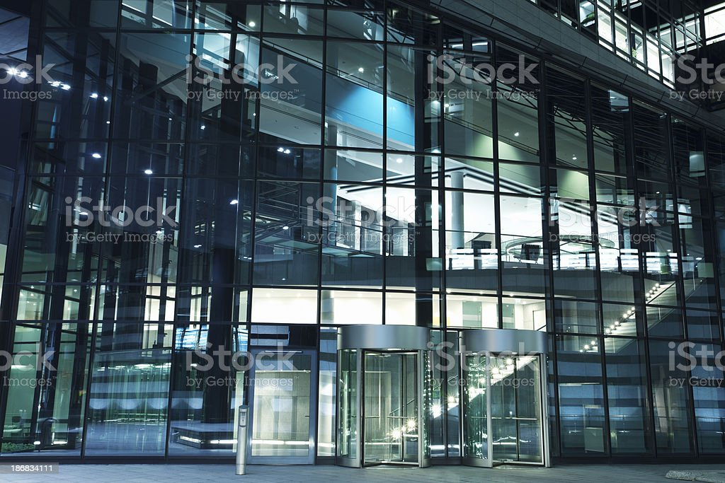 Modern Office Building Entrance with Revolving Doors at Night royalty-free stock photo
