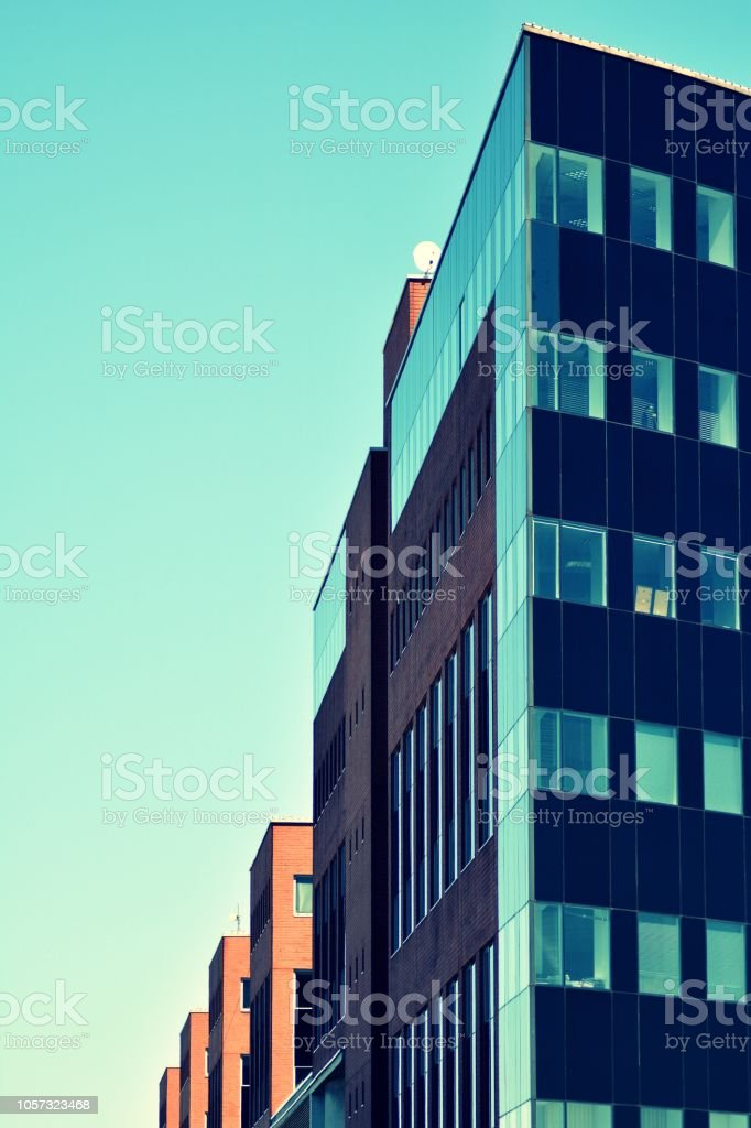 Modern office building on a clear sky background. Retro stylized colorful tonal filter effect stock photo