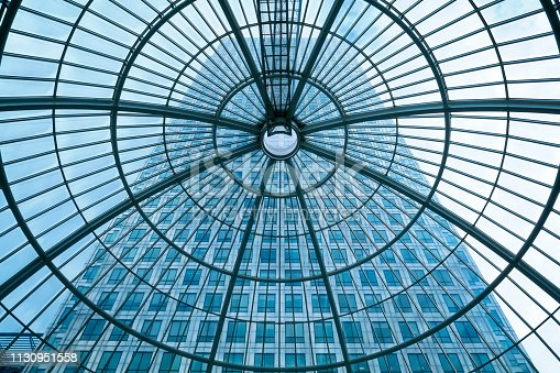 Office building seen through glass roof, glass ceiling in public building, low angle below, Canada Tower, financial district in Canary Wharf, blue toned image, London, England, UK.
