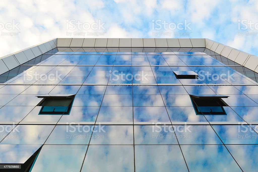 Modern office building with clouds reflected on it stock photo