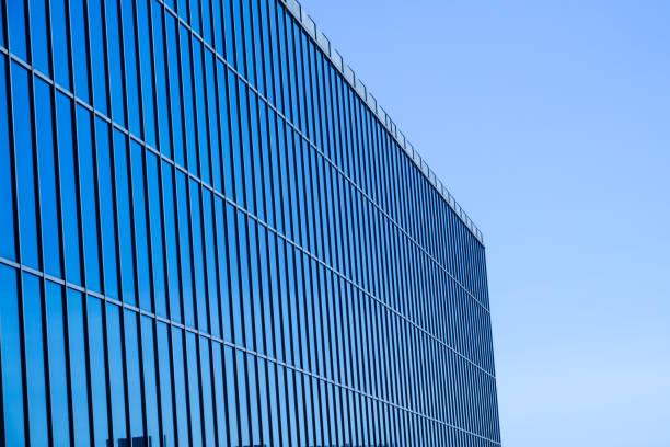 moderne bürogebäude in der stadt mit reflexion der anderen gebäude in blauen glasfenster und glaswand mit weißen wolken - liebeskummer englisch stock-fotos und bilder