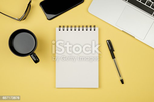 Modern office desk table with laptop, blank notebook page for input the text in the middle and other supplies. Top view, flat lay