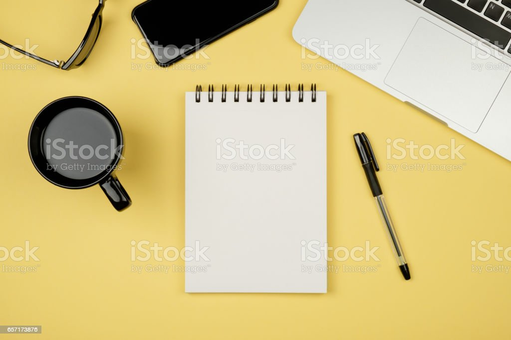 Modern office desk table with laptop, blank notebook page for input the text in the middle and other supplies. Top view, flat lay стоковое фото