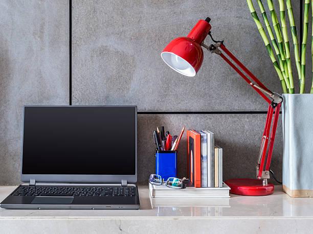 Nowoczesne Biuro biurku z laptopa, lampa i Wazon kwiatów – zdjęcie