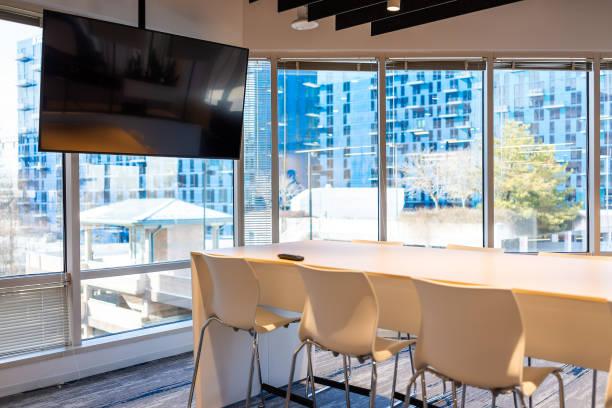 Escritório moderno no edifício com reunião de madeira a tabela corporativa do negócio com tela e cadeiras da televisão esvaziam ninguém - foto de acervo