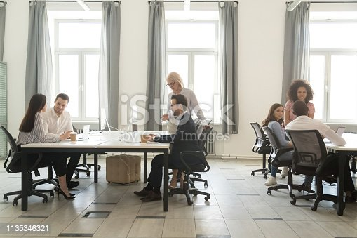 1090214584 istock photo Modern office interior with business team people working on computers 1135346321