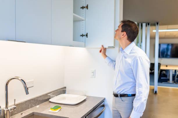 moderna kontor kök rum i byggnad med man öppning hyllskåp av kran tittar inuti - looking inside inside cabinet bildbanksfoton och bilder