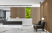 istock Modern Office lobby interior with long wooden planks background and reception desk with green Eco plant moss wall 1280635859