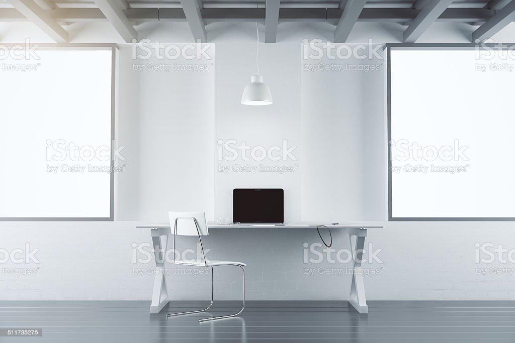 Bureau moderne avec un mobilier blanc affiche un ordinateur portable