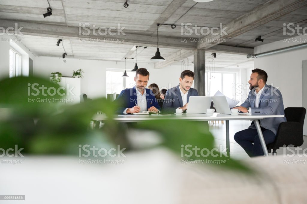 Modern office space with people working Modern office space with people working. Businesspeople sitting at a table and having meeting. Adult Stock Photo