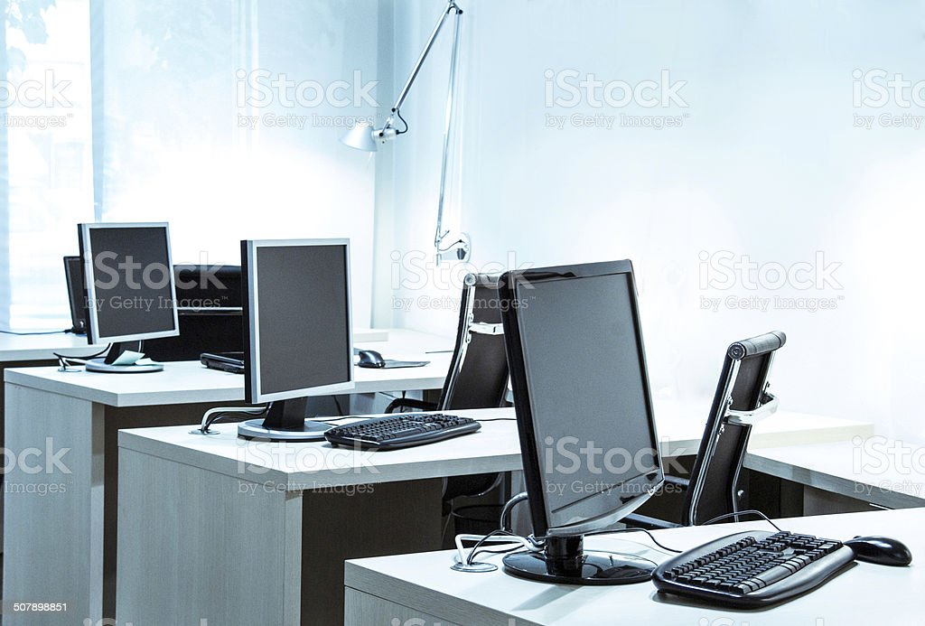 modern office with computers and desks in blue toned space stock photo