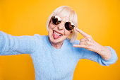 istock Modern old lady take selfie picture showing sign rock and roll isolated on bride yellow background 1041010510