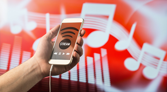 istock Modern online music streaming concept. Close up of a man holding smartphone in hand and listening to music with mobile app. Red blurred note background. 673437050